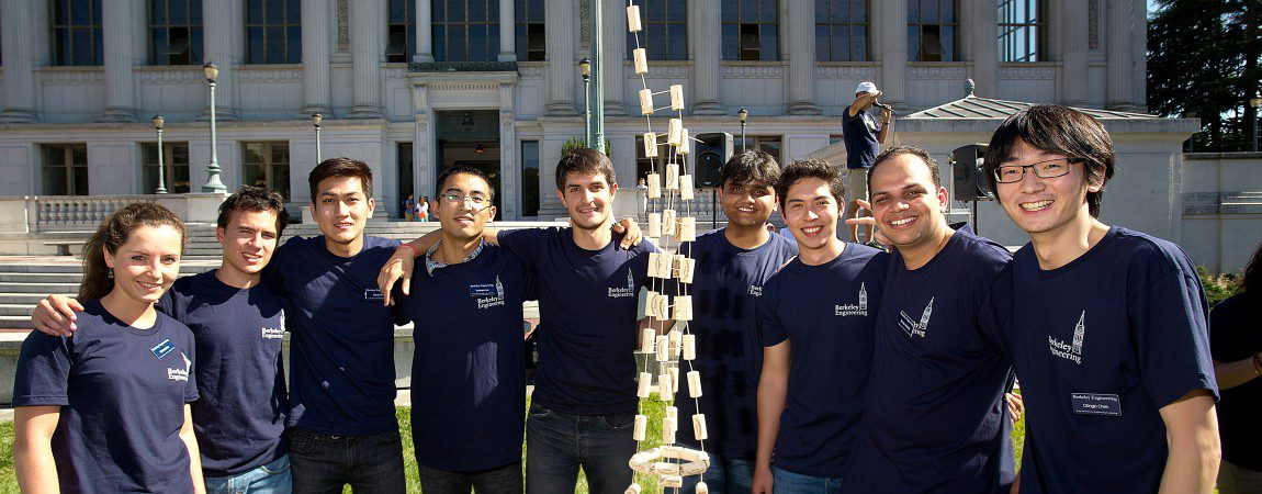 a group of students in Berkeley Engineering shirts smiling outside Doe Library