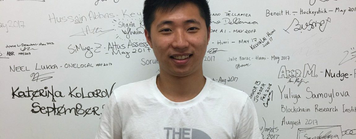 Louis Huang standing in front of a whiteboard