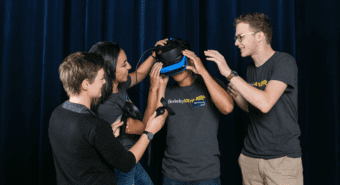 One student uses a virtual reality headset while three other students assist him.