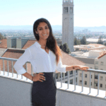 Tara poses by a railing; in the background is Berkeley campus and the campanile.